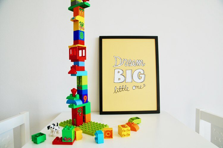Gul poster med texten Dream big little one placerad på bord med färgglad duplo lego